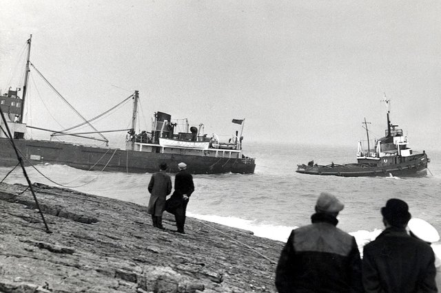 A tug boat tries to pull the cargo ship, Yewglen, from rocks at Beadnell Point on February 29, 1960. Picture: Brian Wood