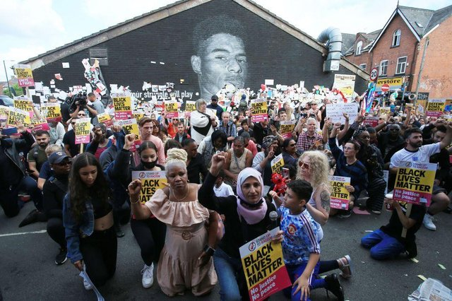 Anti-racism protestors demonstrate by a mural of England forward Marcus Rashford after it was defaced on July 13. (Photo by LINDSEY PARNABY/AFP via Getty Images)