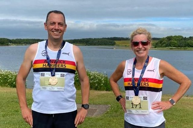 Alnwick Harriers at Druridge Bay with their medals.