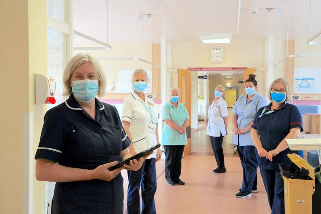 Sue Gibson, left in dark blue, Anna Wood, right in dark blue, and other staff on the ward before moving out.